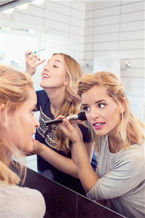 Young female friends applying makeup in mirror Stock Photo - Premium Royalty-Free, Code: 698-07944521