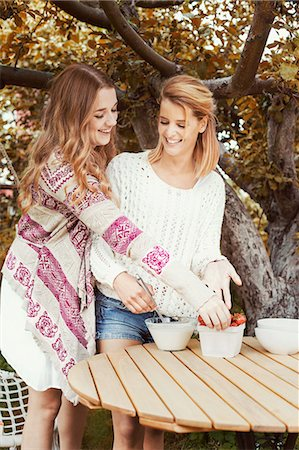 Happy sisters preparing smoothie at outdoors table Stock Photo - Premium Royalty-Free, Code: 698-07944523