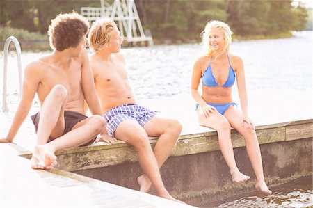 Friends talking while sitting on boardwalk at lake Stock Photo - Premium Royalty-Free, Code: 698-07944530