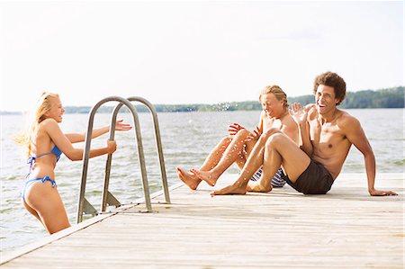 Playful friends on boardwalk at lake Stock Photo - Premium Royalty-Free, Code: 698-07944531