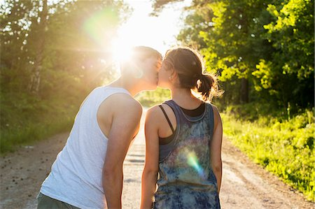 Rear view of couple kissing on dirt road against bright sun Stock Photo - Premium Royalty-Free, Code: 698-07944555