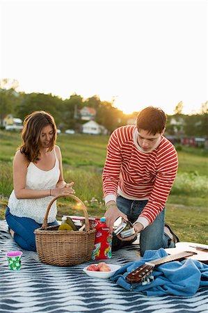 Couple enjoying picnic on field Stock Photo - Premium Royalty-Free, Code: 698-07944566