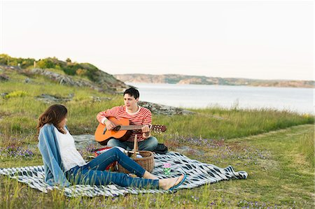 Man playing guitar for girlfriend while enjoying picnic Stock Photo - Premium Royalty-Free, Code: 698-07944567