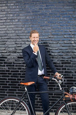 Portrait of happy businessman talking on mobile phone while standing on sidewalk with bicycle Stock Photo - Premium Royalty-Free, Code: 698-07944624