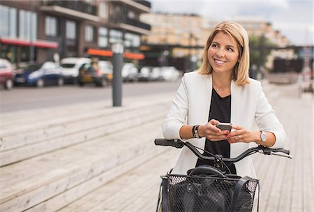 Smiling businesswoman using smart phone in city Stock Photo - Premium Royalty-Free, Code: 698-07944627
