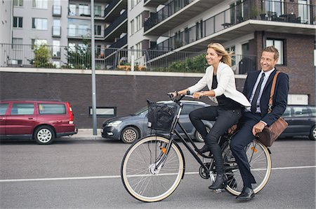 photography - Happy business people riding on bicycle in city street Stock Photo - Premium Royalty-Free, Code: 698-07944634
