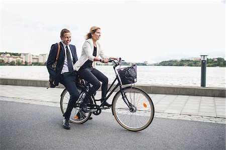 Happy business people riding on bicycle in city street Stock Photo - Premium Royalty-Free, Code: 698-07944635