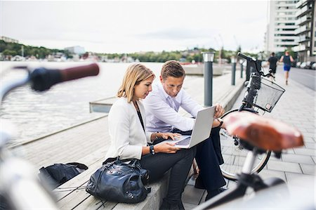 europe - Business people working on laptop against clear sky Stock Photo - Premium Royalty-Free, Code: 698-07944638