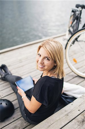 portrait - Portrait of smiling businesswoman using digital tablet while sitting on steps Stock Photo - Premium Royalty-Free, Code: 698-07944639
