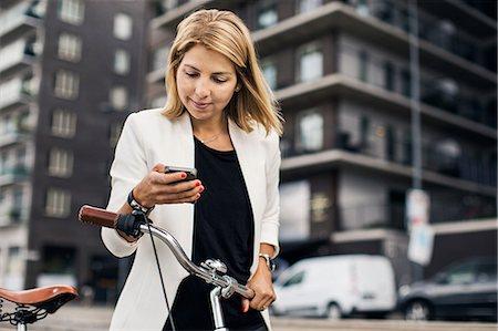 photography - Businesswoman using smart phone in city Stock Photo - Premium Royalty-Free, Code: 698-07944632