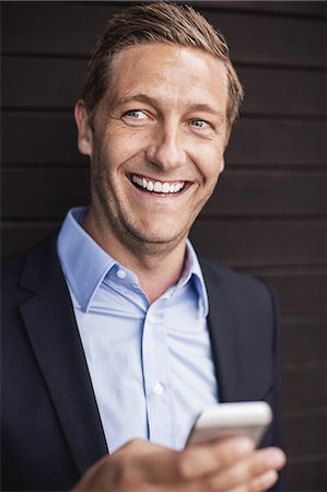 portrait smile caucasian one - Happy businessman using smart phone Stock Photo - Premium Royalty-Free, Code: 698-07944646
