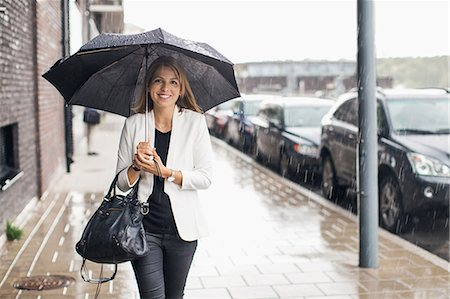 people with umbrellas in the rain - Portrait of smiling businesswoman walking on sidewalk with umbrella during rainy season Stock Photo - Premium Royalty-Free, Code: 698-07944642