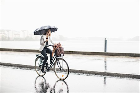 people with umbrellas in the rain - Full length of businesswoman riding bicycle on wet city street during rainy season Stock Photo - Premium Royalty-Free, Code: 698-07944643
