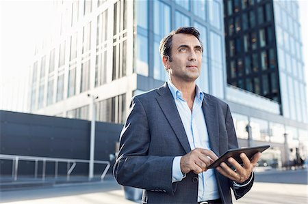 Confident businessman looking away while using digital tablet outside office building Stock Photo - Premium Royalty-Free, Code: 698-07944654