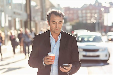 Businessman using mobile phone and holding disposable coffee cup while walking on city street Foto de stock - Sin royalties Premium, Código: 698-07944664