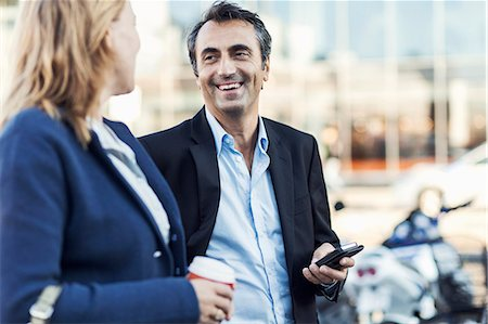 Happy businessman talking to female colleague outdoors Stock Photo - Premium Royalty-Free, Code: 698-07944665