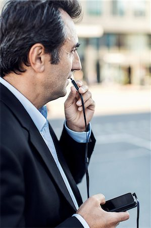 Side view of businessman communicating through headphones using mobile phone on street Stock Photo - Premium Royalty-Free, Code: 698-07944669
