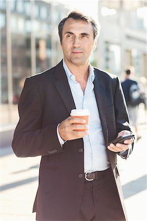 Businessman looking away while holding mobile phone and disposable coffee cup on city street Stock Photo - Premium Royalty-Free, Code: 698-07944663