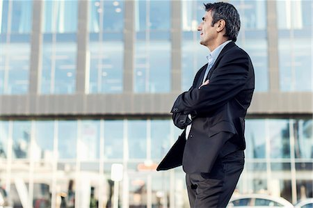 Businessman with arms crossed looking away outside office building Stock Photo - Premium Royalty-Free, Code: 698-07944674