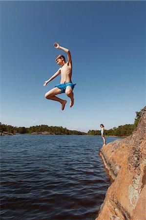 Boy jumping into lake Stock Photo - Premium Royalty-Free, Code: 698-07944678