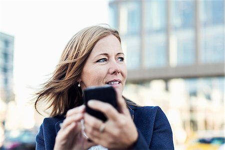 Businesswoman looking away while using mobile phone outdoors Stock Photo - Premium Royalty-Free, Code: 698-07944673
