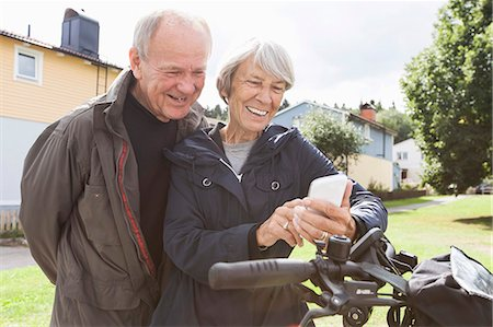 Happy senior couple using mobile phone by bicycle at yard Stock Photo - Premium Royalty-Free, Code: 698-07944688