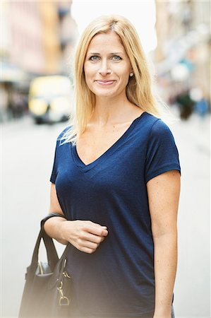 Portrait of smiling mid adult woman standing on street in city Stock Photo - Premium Royalty-Free, Code: 698-07944698