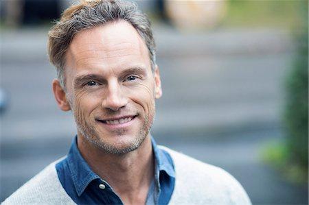 Portrait of smiling man on street Stock Photo - Premium Royalty-Free, Code: 698-07944714