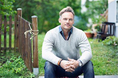 Portrait of smiling mature man sitting in yard Stock Photo - Premium Royalty-Free, Code: 698-07944710