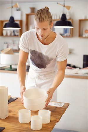 Young man holding craft products in crockery workshop Stock Photo - Premium Royalty-Free, Code: 698-07944753