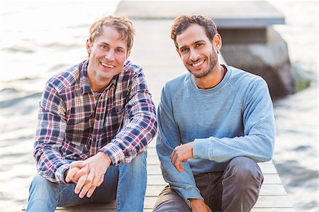 Portrait of happy male friends sitting on pier Stock Photo - Premium Royalty-Free, Code: 698-08007817