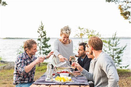 Happy woman serving beer to friends during lunch at lakeshore Stock Photo - Premium Royalty-Free, Code: 698-08007827