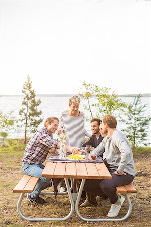 Happy friends having lunch at lakeshore Stock Photo - Premium Royalty-Free, Code: 698-08007828
