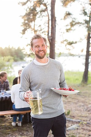 Portrait of happy man holding beer jug and strawberries with friends sitting at picnic table in background Stock Photo - Premium Royalty-Free, Code: 698-08007829