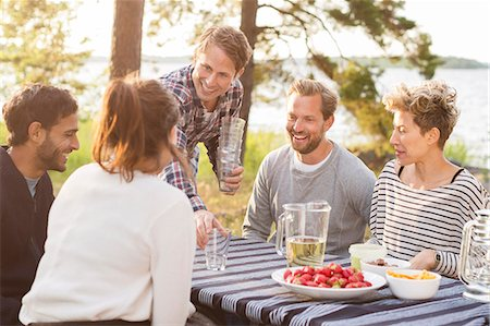 Group of friends enjoying while having lunch at lakeshore Stock Photo - Premium Royalty-Free, Code: 698-08007834
