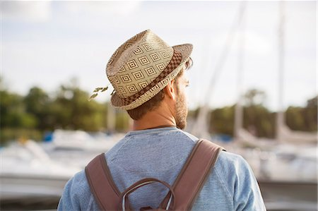 Rear view of man wearing hat and backpack at harbor Stock Photo - Premium Royalty-Free, Code: 698-08007837