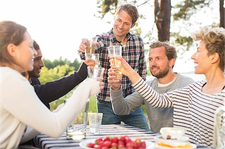 Group of happy friends toasting beer glasses during lunch at picnic table Stock Photo - Premium Royalty-Free, Code: 698-08007832