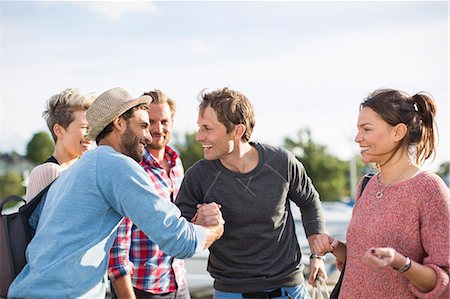 Happy friends greeting each other against sky Stock Photo - Premium Royalty-Free, Code: 698-08007844