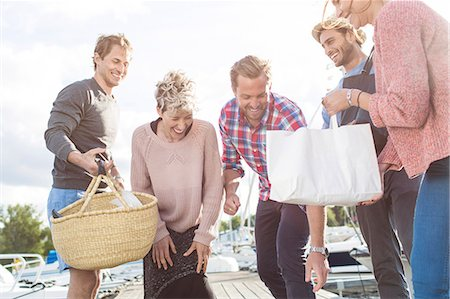 Happy friends preparing for picnic on pier at harbor Stock Photo - Premium Royalty-Free, Code: 698-08007854