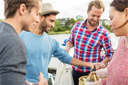 Happy friends with picnic basket outdoors Stock Photo - Premium Royalty-Free, Code: 698-08007855