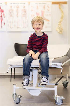 Portrait of happy boy sitting on examination table in orthopedic clinic Stock Photo - Premium Royalty-Free, Code: 698-08007864