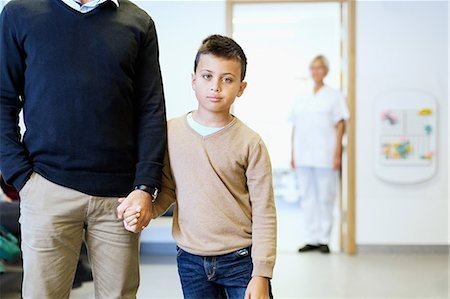 doctor in waiting room - Portrait of boy holding father's hand with nurse in background at orthopedic clinic Stock Photo - Premium Royalty-Free, Code: 698-08007886