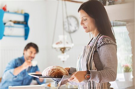 Woman holding freshly baked bread in tray with man in background at home Stock Photo - Premium Royalty-Free, Code: 698-08007906