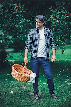 Full length of man carrying wicker basket at apple orchard Stock Photo - Premium Royalty-Free, Code: 698-08007954