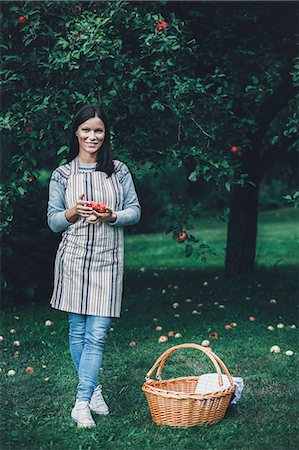 Full length portrait of smiling woman holding fresh apples at orchard Stock Photo - Premium Royalty-Free, Code: 698-08007957