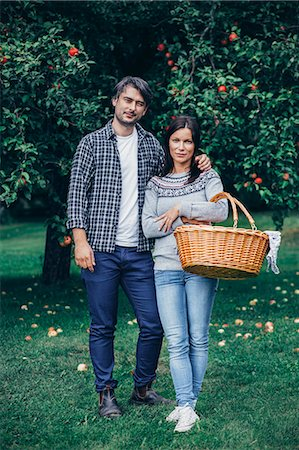 Portrait of couple standing with wicker basket at apple orchard Stock Photo - Premium Royalty-Free, Code: 698-08007951