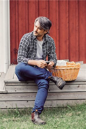 farm phone - Thoughtful farmer with wicker basket holding mobile phone while sitting on porch at yard Stock Photo - Premium Royalty-Free, Code: 698-08007952