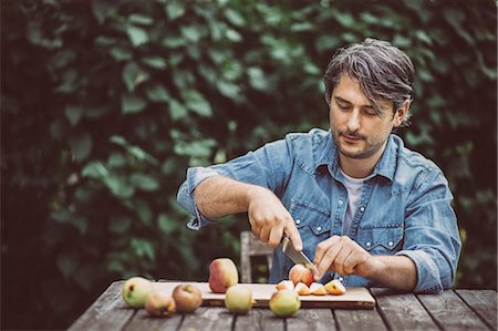 Mid adult man cutting apples at table in organic farm Stock Photo - Premium Royalty-Free, Code: 698-08007963