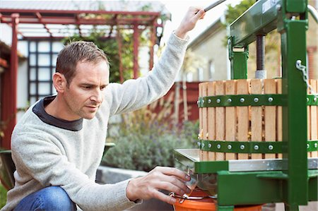 Male farmer collecting fresh apple juice from cider in glass at yard Stock Photo - Premium Royalty-Free, Code: 698-08008006