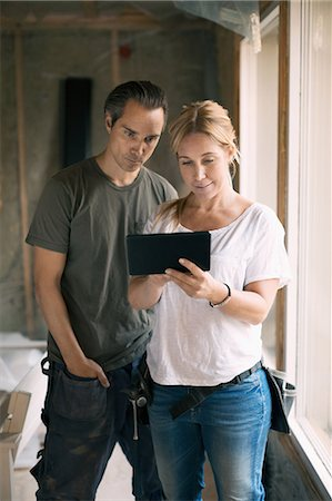 Couple using digital tablet in house being renovated Stock Photo - Premium Royalty-Free, Code: 698-08008063